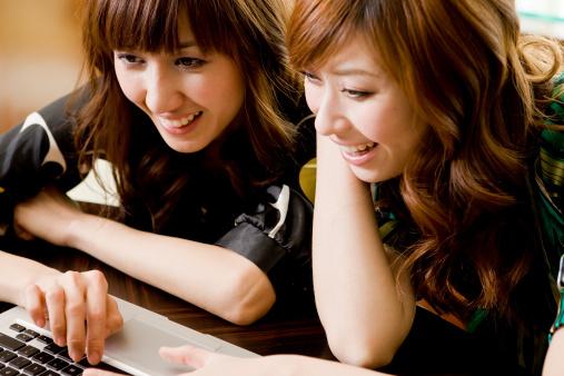 meninas dando risada em frente ao computador - imagem: Btrenkel/Vetta